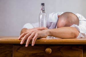 Man with addiction slumped on table with bottle of alcohol addiction